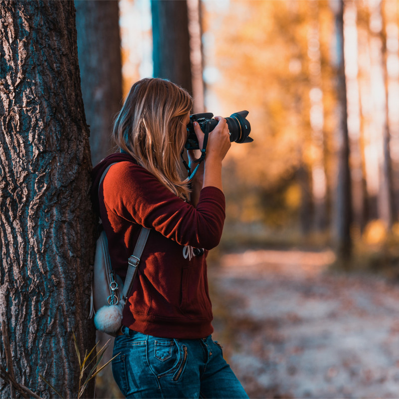 Woman with camera taking photos in the woods