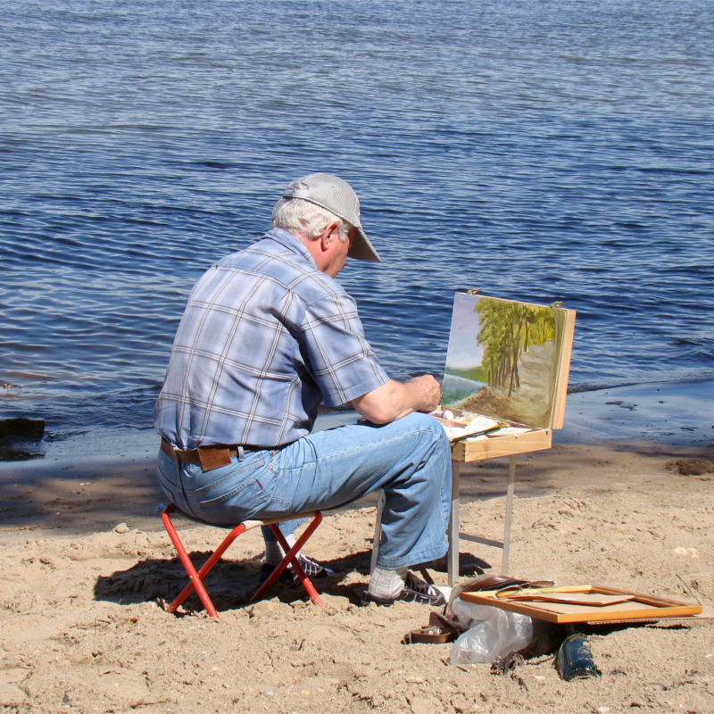 View from behind, artist painting on by seashore, ocean in background